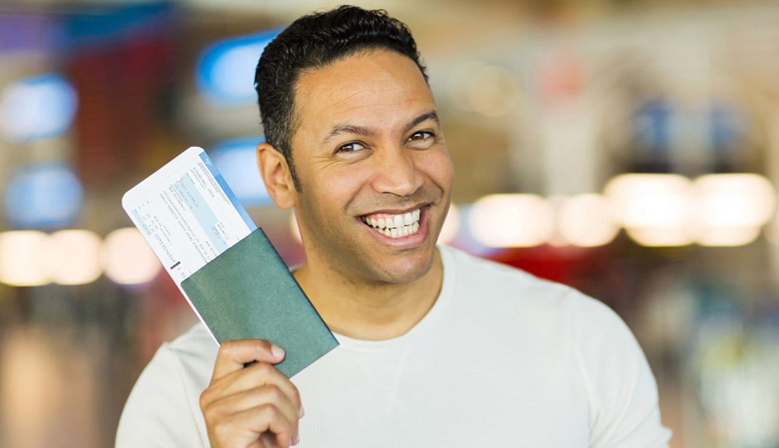 mid age man holding passport and boarding pass