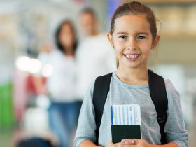 little girl holding passport and boarding pass
