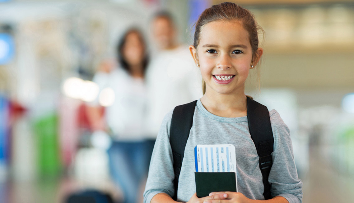 little girl holding passport and boarding pass